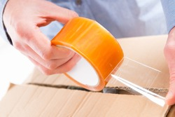 Hands with roll of transparent packaging, adhesive tape.