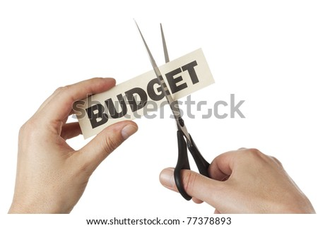 "hands with scissors cutting label signed ""Budget"" isolated"