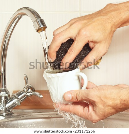 Hands with sponge wash the cup under running water in the kitchen