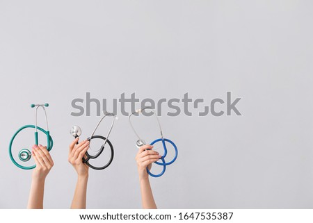 Hands with stethoscopes on grey background