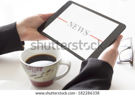 Hands with tablet and coffee reading news