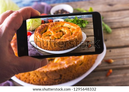 Hands with the phone takes pictures of a pie.Traditional homemade open pie with cabbage and sauerkraut on the plate on the rustic wooden background.
