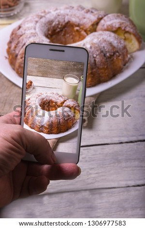 Hands with the phone takes pictures of a pie.Traditional homemade sweet round fruit cake on the plate on the rustic wooden background. Vertical