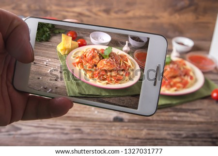 Hands with the phone takes pictures of Italian cuisine spaghetti with meatballs noodles pasta meal in a plate on a rustic wooden background.