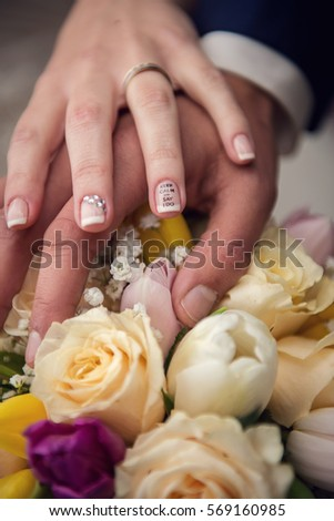 Hands with wedding rings and bouquet from roses #569160985