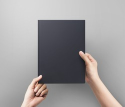 Hands women holding black book cover blank top view.  Blank book cover.