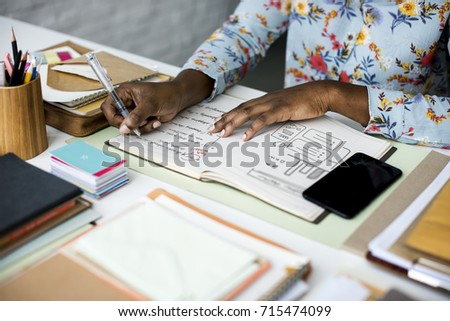 Hands Working on Office Desk with Notebooks and Stationery on White Table