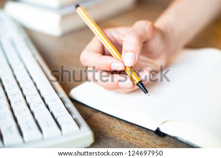 Hands writes a pen in a notebook (computer keyboard, a stack of books in background)