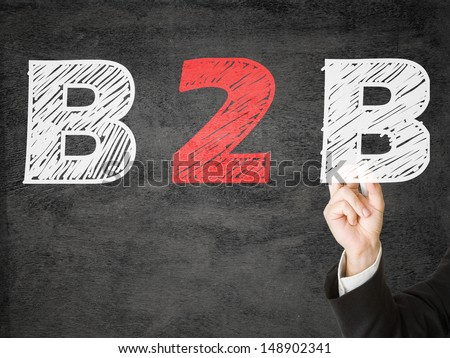 Hands writing B2B - business to business - on transparent screen