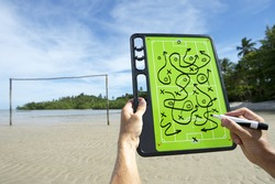 Hands writing crazy soccer match plans on football tactics board on rustic Brazil beach football pitch