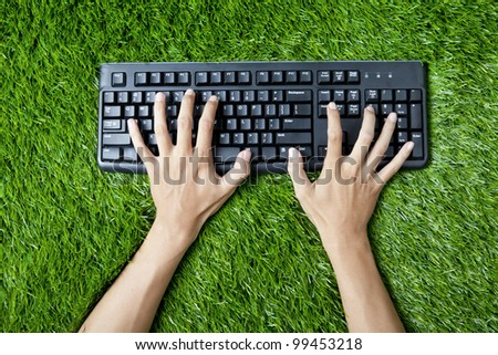 Hands writing on a computer keyboard. Shot on the green grass