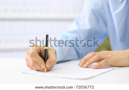 Hands writing on a paper