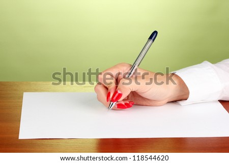 Hands writing on  paper on green background