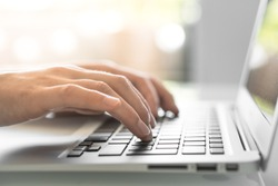 Hands writing ond a keyboard of a laptop or a notebook in Home Office