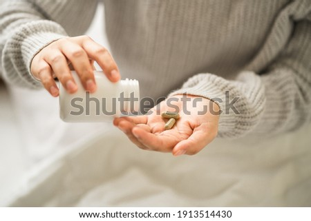 hands young women holding medical capsules, female taking supplement product or vitamin type capsule.  ストックフォト ©