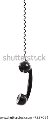Handset piece from an old phone suspended by the phone cord, isolated on white background