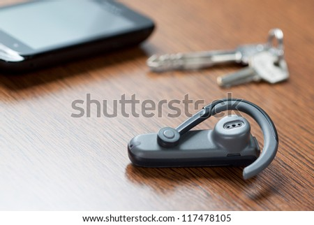 Handsfree with mobile phone and car keys in background