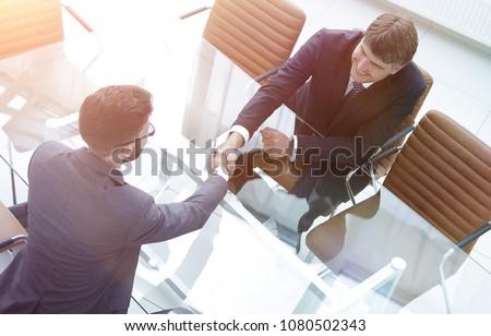 Handshake across the table of financial partners