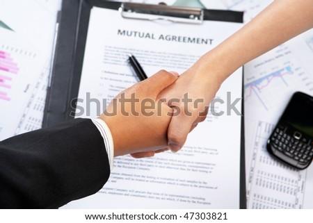 Handshake between businesswoman\'s hand over agreement and other document