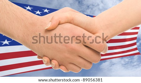 Handshake between man and woman on background of American flag in sky