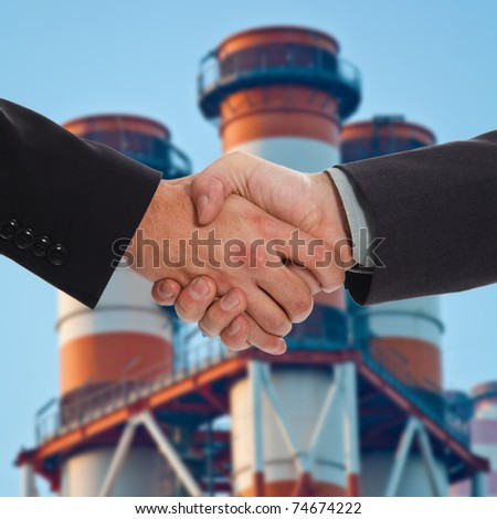Handshake between two businessmen. Chimneys in the background.