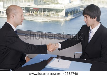 Handshake between two businessmen in a stylish office with harbour in the background