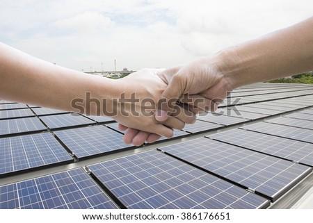Handshake - Hand holding on Blue solar panels background.