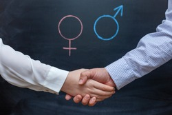 Handshake of a man and a woman against a background of gender symbols. Concept of gender equality