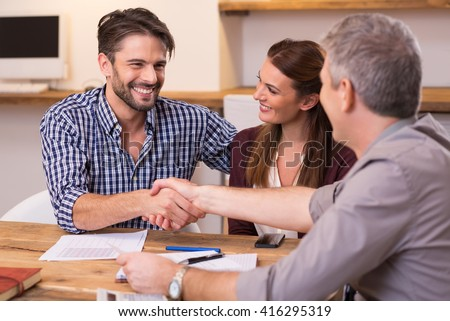 Handshake of a mature manager with a happy young couple at office. Businessmen handshake during meeting signing agreement. Happy man shaking hands whit his finacial advisor.