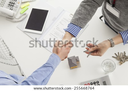 Handshake of a real estate agent and a visitor