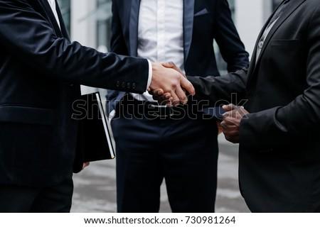 Handshake of business partners. Three businessmen close-up Сток-фото ©