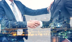 Handshake of 2 businessman in a black suit at the meeting room, office located the business center city.mergers and acquisitions for start greeting with good etiquette negotiation the success of both