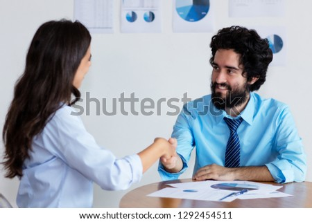 Handshake of turkish businessman and businesswoman at office of company