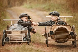 Handshake of two boys racers on their homemade wooden car. Retouch for retro