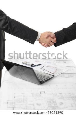 Handshake of two business partners after signing a contract. Focus on the documents
