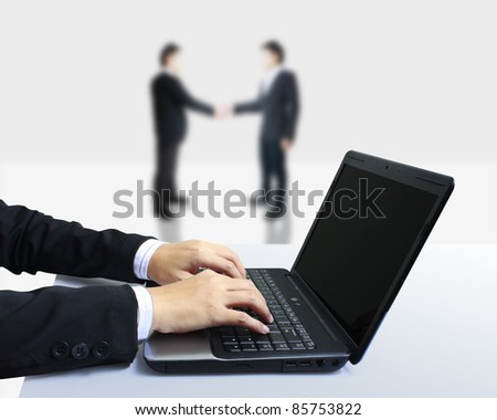 Handshake of two business with a laptop