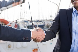 handshake of two businessmen near the yachts in the port