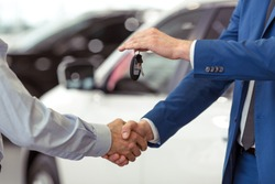 Handshake of two businessmen when selling a car in a motor show, close-up