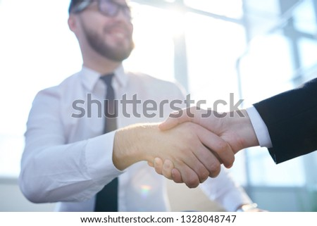 Handshake of young successful brokers or traders congratulating one another on new business deal