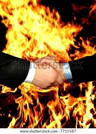 handshake on a background a fire
