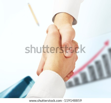 handshake on background of graphs and charts