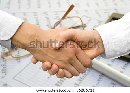 handshake over paper and pen,blurry computer in the background