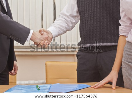 Handshake partners in the office after the signing of important documents - two people on one side and one on the other