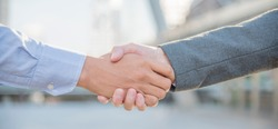 Handshake partnership team business partners shaking hands together greeting start up business. Corporate teamwork partnership outside office modern city as background. Businessman with hands shaking