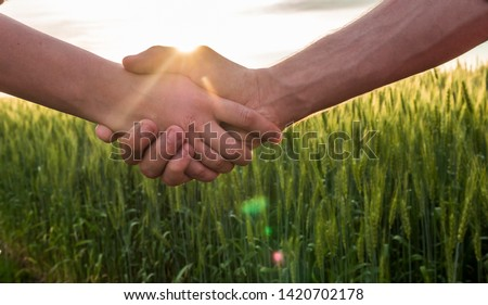 Handshake two farmer on the background of a wheat field with sun glare #1420702178