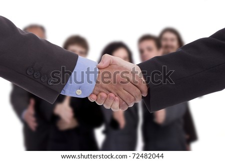 Handshake, with business team in background