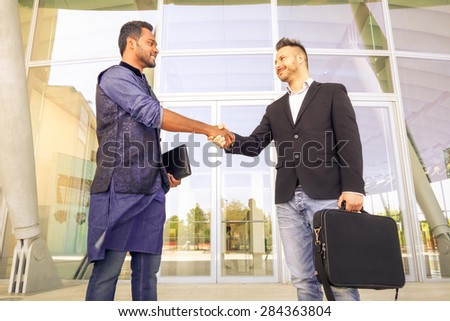 Handshaking between two young businessmen holding laptop - Concept of modern global market - Outdoor trade meeting between men of different race and culture - happy students shaking hands in the city