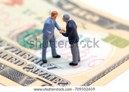 Handshaking businessmen on usa dollar banknote. Business company profitable deal. Financial agreement for buy and sell. Profitable deal concept. Investment profit. Financial transaction. Cash profit