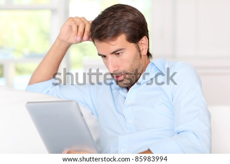 Handsom guy using electronic tablet at home