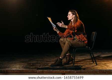 handsome actor with scenario playing on stage during rehearse in theatre Сток-фото ©